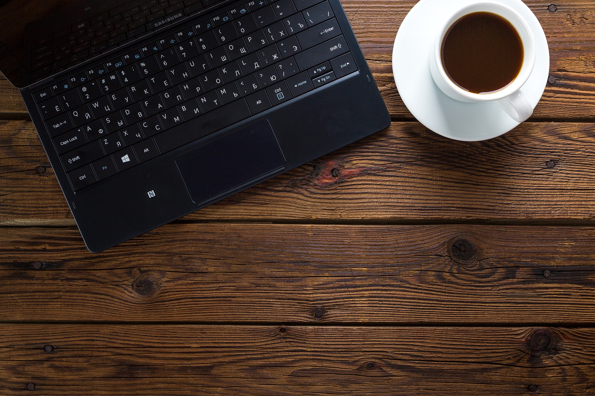black laptop beside a cup of coffee placed at the office table